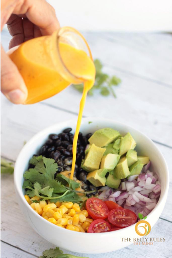 pouring dressing on black bean corn salad