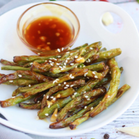 A plate of Air Fryer Green Beans and Chili Garlic Sauce