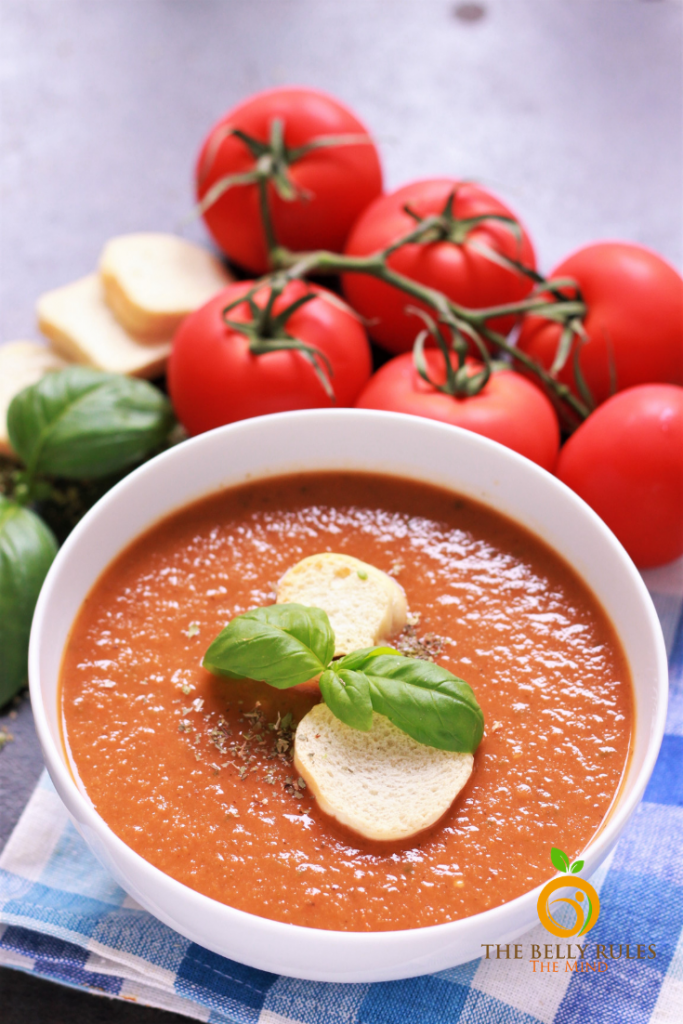 Tomato Basil Soup in a bowl with tomatoes and basil on the side